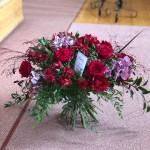Stående bukett i röda toner och orkideér