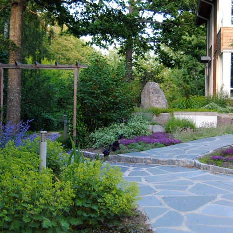 Entréträdgård med gångar i Offerdalsskiffer och stora perenneplanteringar
