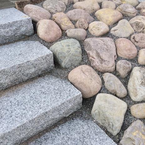Kullersten och trappa i granitblock.