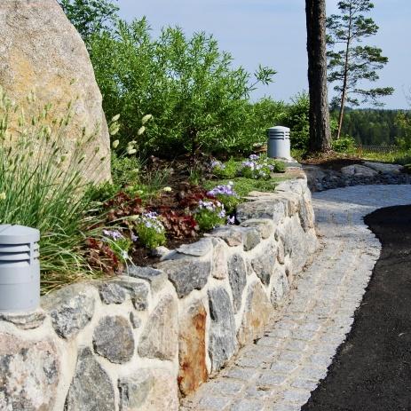 Naturstensmur och kant mellan mur och asfalt i smågatsten.