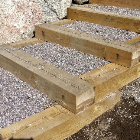 Svängd trappa med grus i kraftig träram.