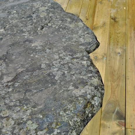 Trätrall som sågats utmed stenhällen.