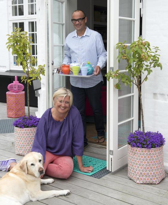 Charlotte och Philippe tillsammans med sin älskade hund, på verandan till sitt fina hus i Odense