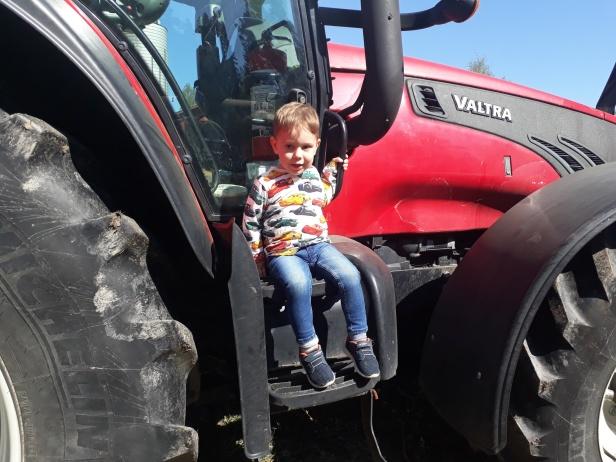 Lycklig Julius får sitta på traktorn.
