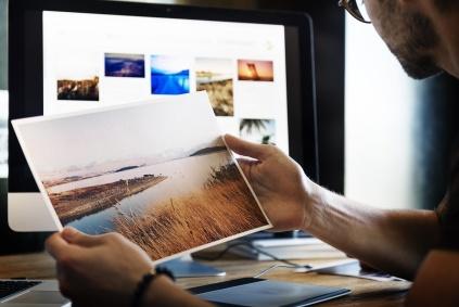 En man sitter vid en dator med många bilder på skärmen och skall välja vilken han gillar.