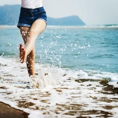 En tjej sparkar vatten vid strandkanten