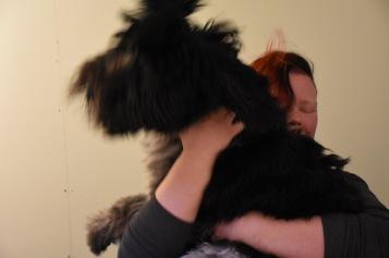 Camilla som driver hunddagiset kramar sin hund.