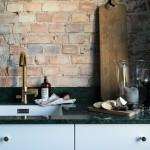 Den gamla tegelväggen i köket har tagits fram och matchas stilfullt ihop med den gröna marmorskivan.