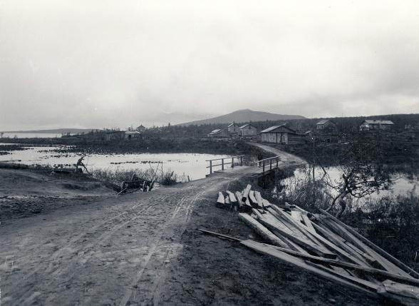 Bron över Luossajoki. I bakgrunden syns  det första bostadsområdet Rälstippen. Foto: Oscar Olsson. 1898. Bildägare: Nordiska museet.