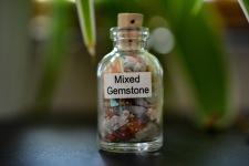 Liten flaska med mixade kristaller