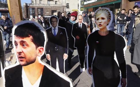 Efrem Lukatsky/AP/TT Pappfigurer som visar presidentkandidaterna Volodymyr Zelenskyj och Julia Tymosjenko står på ett torg i huvudstaden Kiev tidigare i mars.