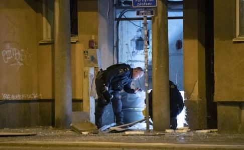 Johan Nilsson/TT Personal från nationella bombskyddet undersöker en port vid Nobeltorget i centrala Malmö efter en explosion.