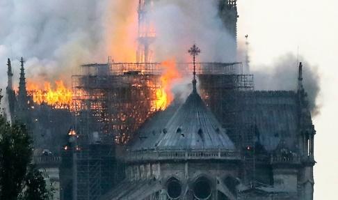Francois Guillot/AFP/TT Rök och lågor stiger från medeltidskatedralen Notre-Dame i Paris.