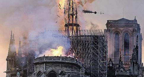 Diana Ayanna/AP/TT Notre-Dames spira kollapsar under branden som rasar i katedralen.