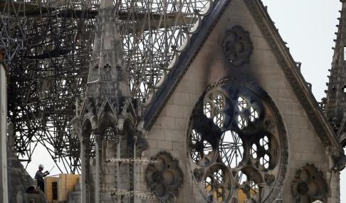 Francois Mori En man kontrollerar den bärande träkonstruktionen i Notre-Damekyrkan efter branden.