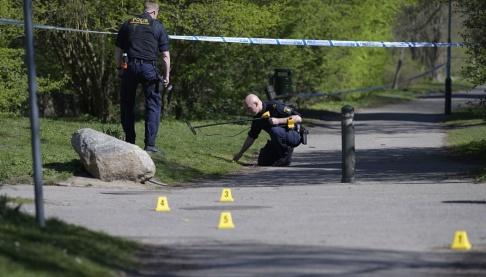 Johan Nilsson/TT Polisens kriminaltekniker undersöker ett avspärrat område i Malmö på långfredagen efter det att polis skjutit en knivbeväpnad man i benet.