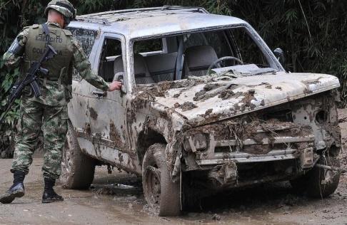 Luis Benavides/AP/TT En soldat undersöker en bil som skadats i ett jordskred i Colombia 2011.