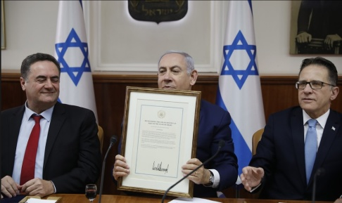 Ronen Zvulun/pool via AP/TT Israels premiärminister Benjamin Netanyahu håller upp den amerikanska kungörelsen, signerad av Donald Trump. Arkivbild från 14 april.