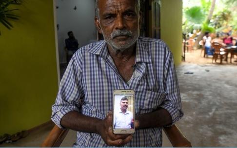 LAKRUWAN WANNIARACHCHI Velusami Raju håller upp en bild på sin telefon av sin son Ramesh Raju som dog i ett av attentaten.