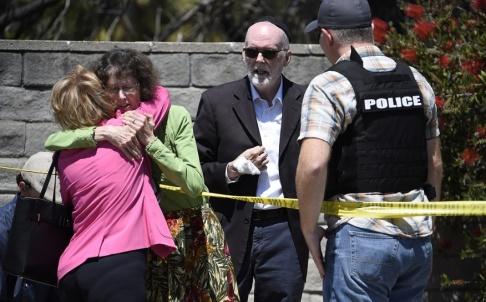 Denis Poroy/AP/TT Människor omfamnar varandra utanför synagogan i Poway vid San Diego i Kalifornien där en dödlig skjutning ägde rum i lördags.