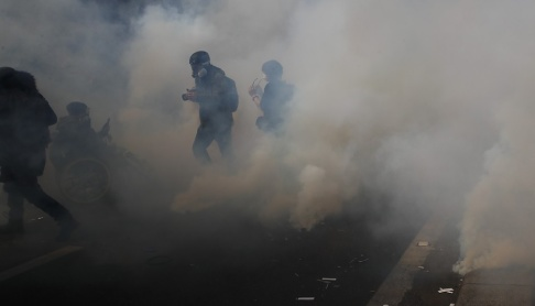 Francois Mori/AP/TT Aktivister flydde från tårgas under en förstamajdemonstration i Paris.
