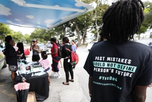 Wilfredo Lee/AP/TT Kampanjarbetare i höstas inför omröstningen om exfångar skulle få rätt att rösta. Arkivbild.