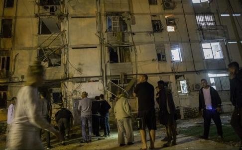 Tsafrir Abayov/AP/TT Israeler utanför ett bostadshus som under natten träffats av raketer.