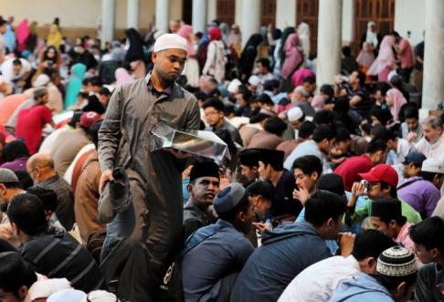 En man bär sin måltid när muslimer samlas för att äta Iftar under Ramadan, vid Al Azhar-moskén i det gamla islamiska området Kairo i Egypten den 12 maj 2019. REUTERS / Mohamed Abd El Ghany.