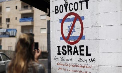 En symbol på en mur i Betlehem som kräver en bojkott av israeliska produkter från judiska bosättningar.  Thomas Coex/AFP/Getty Images
