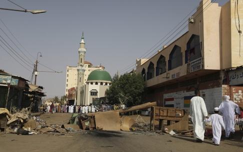 Foto: AP Vuxna och barn kryssar mellan barriärer uppsatta av demonstranter för att hindra militären från att ta sig in i på en av Khartoums huvudgator.