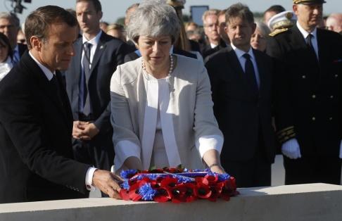Philippe Wojazer/AP/TT Storbritanniens premiärminister Theresa May och Frankrikes president Emmanuel Macron lägger en krans vid minnesceremonin för de brittiska offren under D-dagen.