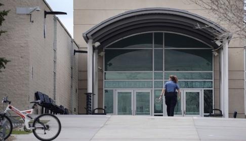 Joe Mahoney/AP/TT En polis patrullerar vid Columbine-skolan i Littleton, Colorado, efter de hot som riktades mot den i april i år. Arkivbild.