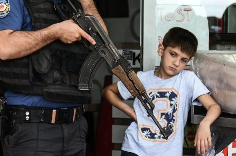En pojke tittar bredvid en polis som håller sin Kalashnikov under en demonstration i solidaritet med kurdiska fångar i Diyarbakir den 24 maj 2019.  Foto av ILYAS AKENGIN / AFP