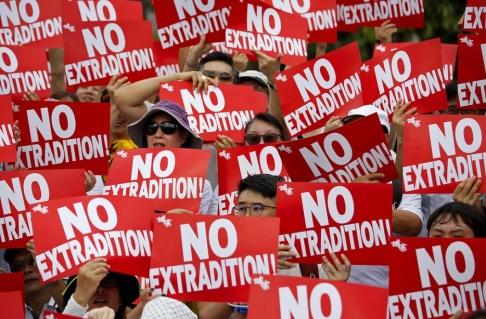 """Demonstranter håller upp skyltar med texten """"No extradition"""" – ingen utlämning."""