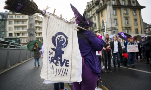 Jean-Christophe Bott/AP/TT Med krav på jämställda löner blockerar strejkande kvinnor en bro i schweiziska Lausanne.