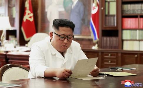 KCNA/Korea News Service/AP/TT Kim Jong-Un läser brevet som påstås ha skrivits av USA:s president Donald Trump. Bilden kommer från Nordkoreas statliga nyhetsbyrå.