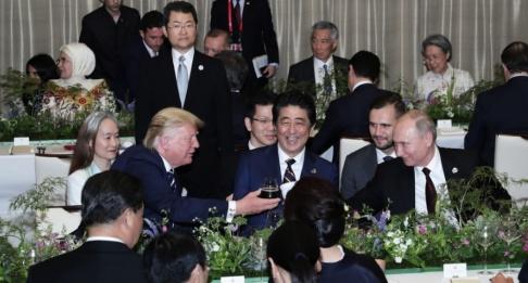 G20-mötet/Reuters/TT Det vinglas USA:s president Donald Trump håller i möter den vita termosmugg som Rysslands president Vladimir Putin håller fram, och som skymtar framför Japans premiärminister Shinzo Abes slips.
