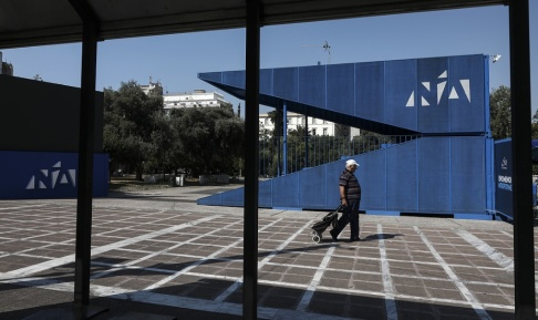 Yorgos Karahalis/AP/TT En man passerar en lokal för förtidsröstning i Aten på lördagen.