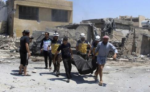 Vita hjämarna/AP/TT En kropp bärs ut efter flyganfall i staden Hish i Idlibprovinsen tidigare i veckan. Arkivbild.