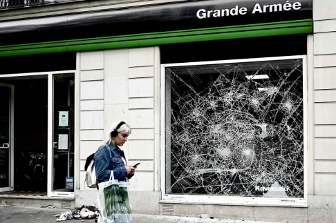 Den här bilden, som togs den 12 juli 2019, visar ett krossat butiksfönster på Grande Armee-gatan, nära Triumfbågen i Paris, där de algeriska anhängarna firade segern för deras lag under 2019 Afrika Cup of Nations (CAN) kvartalsfinal match Elfenbenskusten och Algeriet den 11 juli 2019. Flera butiker i närheten av Champs-Elysées i Paris plundrades dessutom. (Foto av Philippe LOPEZ / AFP)