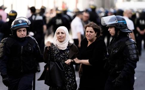 Kenzo Tribouillard/AFP/TT Kvinnor som deltagit i Svarta västarnas aktion leds bort av polis.