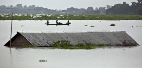 Anupam Nath Bybor ror förbi ett hus i östra delstaten Assam i Indien, som drabbats hårt av regnen.