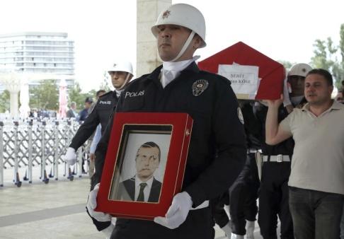 Burhan Ozbilici/AP/TT En polis bär en bild av den turkiske diplomat som dödades i Erbil inför mannens begravning i Ankara.