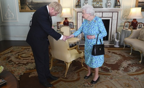 Victoria Jones/Pool via AP/TT Boris Johnson bugar när han hälsar på Elizabeth II.
