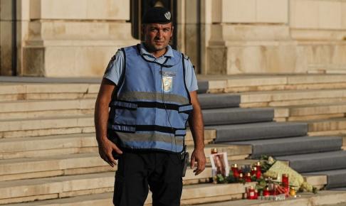 Vadim Ghirda/AP/TT En rumänsk polis utanför inrikesdepartementet i Bukarest den 26 juli 2019. Bredvid honom har blommor och ljus placerats till minne av den 15-åriga flicka som dött efter att hon blivit kidnappad.