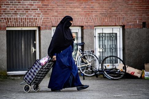 En kvinna med burka i Rotterdam den 29 juli 2019. Ansiktsbeläggningar kommer att förbjudas i Nederländerna från kollektivtrafik, skolor, sjukhus och regeringsbyggnader från och med den 1 augusti 2019. Det nederländska islamiska politiska partiet NIDA har meddelat en plan för att betala för alla böter som mottagits av bärare av burka och niqab. EPA / ROBIN UTRECHT