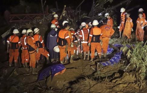Räddningsarbetare jobbar efter ett jordskred i östra Myanmar.