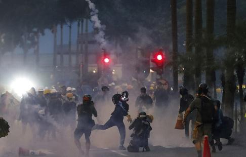 Vincent Thian/AP/TT En demonstrant kastar tårgas avfyrad av polis under demonstrationerna på söndagen, då vilda protester återigen tog över gatorna i Hongkong.