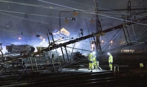 Johan Nilsson/TT Under natten till torsdagen pågick arbete vid de kontaktledningar som fallit ner över spåren norr om stationen i Hässleholm i samband med en våldsam brand i en industribyggnad.