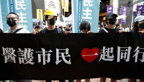 Vincent Thian/AP/TT Demonstranter visar sin solidaritet med en kvinnlig demonstrant, som fått en projektil i ögat, genom att sätta en lapp för sitt ena öga.